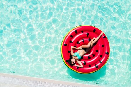 Aerial top of woman wearing a hat sitting in inflatable watermelon in deep cyan calm waters like a pool