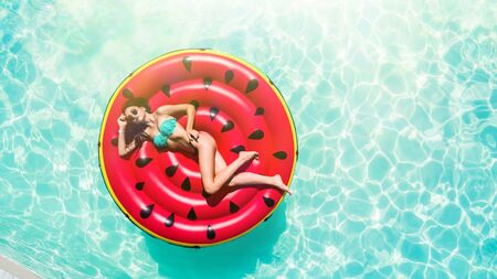 Young sexy woman relaxing in a swimming pool leisure on a big watermelon float Stock fotó
