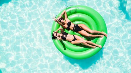 Aerial view of young woman lying on inflatable green mattress floating and relaxing in swimming pool Stock fotó