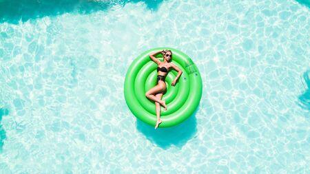 Portrait of a beautiful woman lying on air mattress in swimming pool Stock fotó
