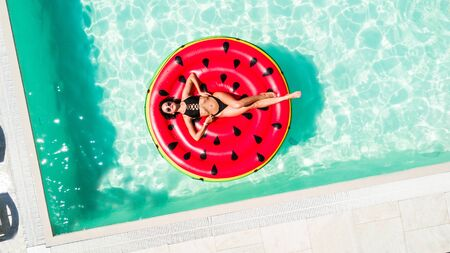 Aerial view of female in bikini lying on a floating inflatable mattress watermelon in swimming pool water.