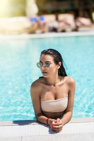 Cute girl in swimming pool with copy space