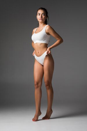 Muscular woman body in lingerie isolated on gray background Zdjęcie Seryjne