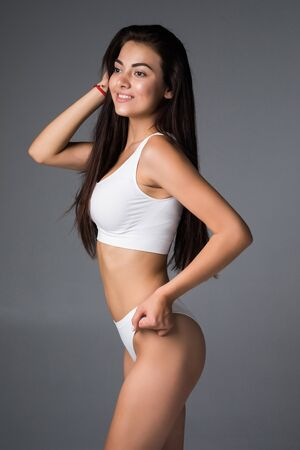 Attractive young brown hair woman in white lingerie posing against grey background and smiling