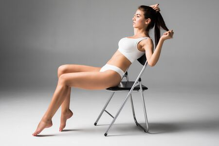 Beautiful woman in white underwear sitting on the chair. Sudio with grey background. 写真素材 - 132843302