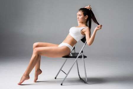 Beautiful woman in white underwear sitting on the chair. Sudio with grey background. 写真素材 - 132843303