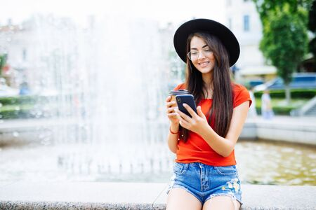 Young woman with phone chating or surf in internet against fountain in the street Standard-Bild