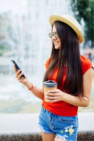 Young pretty woman holding phone and cup of coffee in the street near fountain