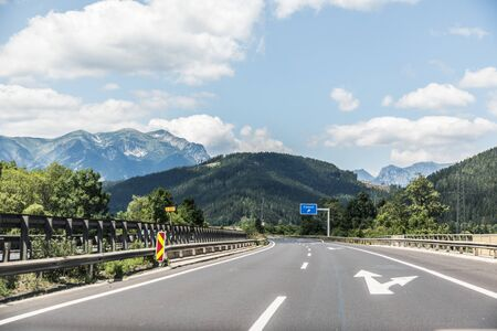 Autobahn or highway with a bridge in the mountains with clear marking surrounded by vibrant green trees under blue sky. Stock Photo