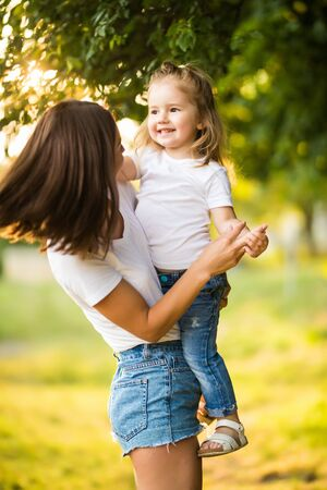 Portrait of beautiful mother with love hugging her precious daughter in bright yellow sunlight in the park, happy family life Фото со стока