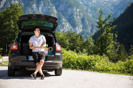 Young travel man sitting in car trunk chating on phone or check mail, surfing in internet while relax on beauty nature landscape
