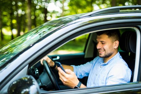 Mann fährt in seinem Auto mit Handy, gefährliche Situation Standard-Bild