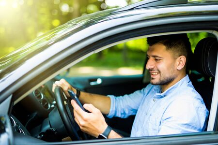 Man driving in his car using cell mobile phone, dangerous situation Standard-Bild