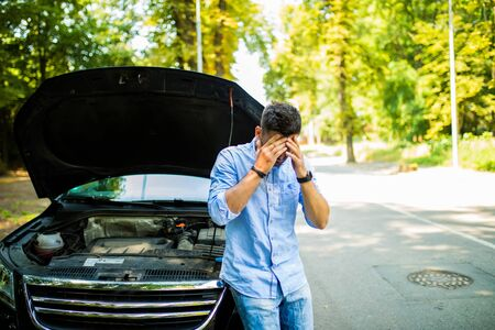 Young man on the road having problem with a car. Broken down car on the road. Traveling problem.