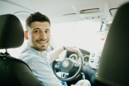 handsome man looking at camera sitting in a car, view from rear seat Archivio Fotografico