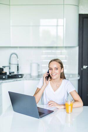Una giovane donna siede al tavolo della cucina usando un laptop e parlando al cellulare.