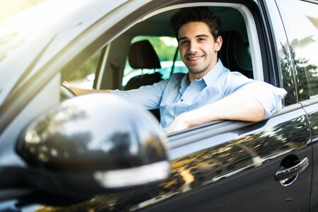 Young handsome man looking straight while driving a car