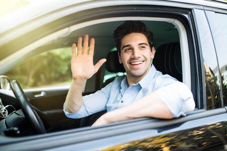 Retrato de joven atractivo morena guapo conduciendo coche y saludando a alguien con la mano. Foto de archivo