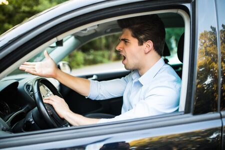 An irritated man driving a vehicle is expressing his road rage.