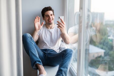 Young man sitting on the windowsill make video call on the phone Standard-Bild
