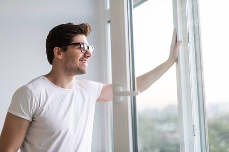 La mano del hombre abre la ventana. Ventilar una casa cuando hace calor.