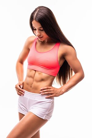 Woman body in sport wear on white with copy space. Sporty girl with slim figure isolated. Perfect abdomen Standard-Bild - 134467410