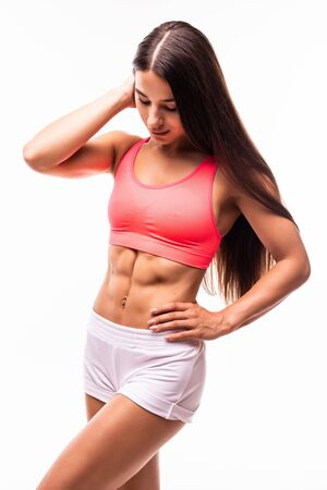 Woman body in sport wear on white with copy space. Sporty girl with slim figure isolated. Perfect abdomen Standard-Bild - 134467412