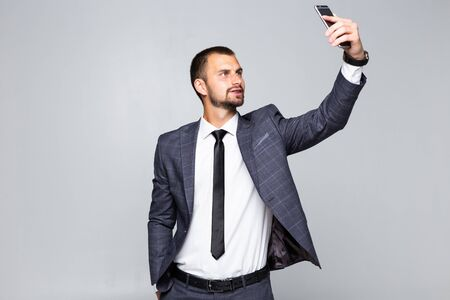 handsome man in suit taking a selfie on isolated background