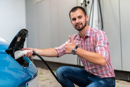Man plugging cable to electric car