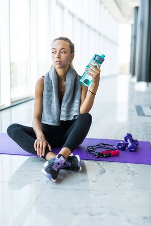 Happy fitness girl sitting relaxed on yoga mat after workout. Woman taking a break after yoga exercises outdoors.