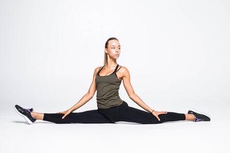 Deportiva joven haciendo práctica de yoga aislada sobre fondo blanco. Foto de archivo
