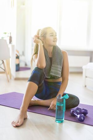 Woman drinking water at the home. Muscular woman taking break after exercise. Smiling attractive fitness woman with towel after training. Jogger run runner energy sweaty yoga vitality wellness concept