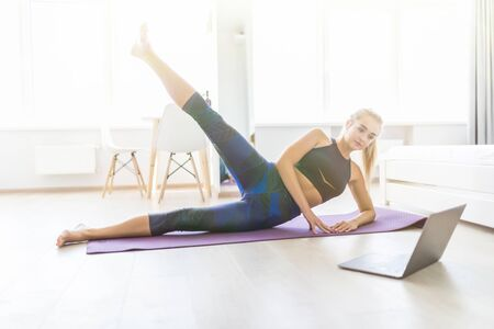 Beautiful woman doing fitness exercise at home Imagens - 136540559