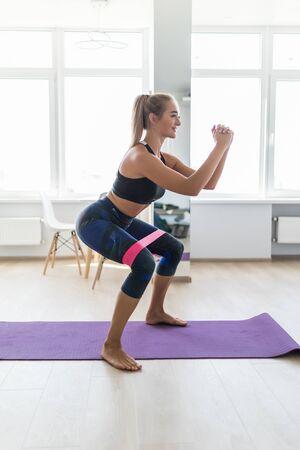 Mujer durante su entrenamiento físico en casa con banda de resistencia de goma