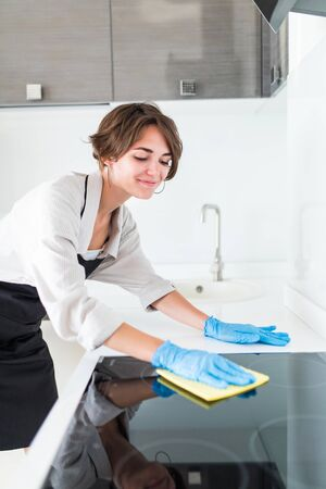 Young woman cleaning kitchen at home Stock Photo