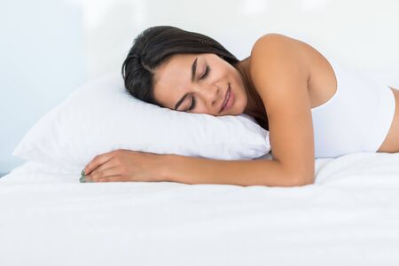 Young woman sleeping on pillow lying in bed at home Stock fotó