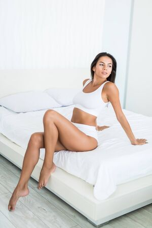 Beautiful woman wearing on white underwear sitting on bed, stretching her hands up Banco de Imagens