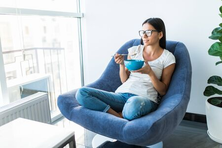 Beautiful, young woman sitting in chair next to the window, having breakfast at home