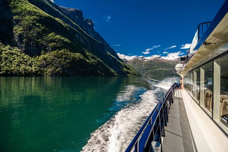Geiranger, Norway - June, 2019: Hurtigruten cruise liner sailing on the Geirangerfjord, one of the most popular destination in Norway and UNESCO World Heritage Site. Geiranger
