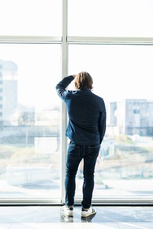 Young businessman standing depressed near window in the office. Stressed and worried about the economic downturn in the future of the company. Stock fotó