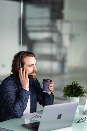 smiling young call center operator in headset working with laptop in office Standard-Bild