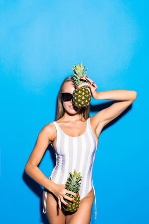 Young woman in summer holidays over blue background holding a pineapple with sunglasses
