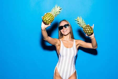 Young sexy woman happy smiling only in glasses posing on blue background with pineapple who cover her breast