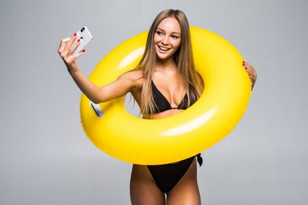 Full length of a happy young girl wearing swimsuit standing taking a selfie while holding inflatable ring isolated over gray background