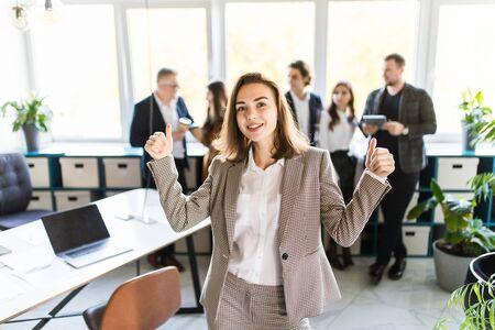 happy businesswoman standing in front of her team.
