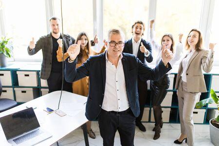 オフィスで彼の同僚の前に立って勝利のジェスチャーを持つ幸せなビジネスマン 写真素材