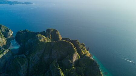 Aerial drone view of tropical turquoise water Maya Bay surrounded by limestone cliffs, Phi Phi islands, Thailand