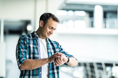Young man looking at wrist watch touching his head being late in office