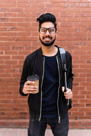 Handsome indian man with backpack and takeaway coffee on street Banque d'images