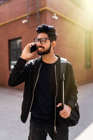 travel, tourism and lifestyle concept - smiling indian man with backpack calling on smartphone on city street Zdjęcie Seryjne